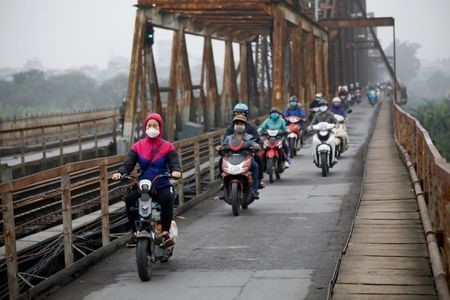 People wear protective masks to protect themselves against coronavirus while driving along Long Bien bridge in Hanoi, March 16, 2020. Reuters/Kham