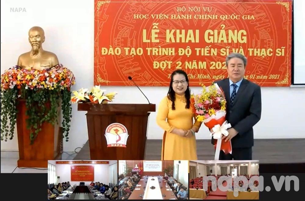 Representative of master students presenting flowers to Dr. Dang Xuan Hoan, NAPA President