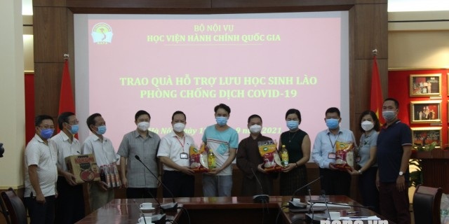Leaders of Dong Da District, Lang Ha Ward, and Monk Thich Dai Thang presenting gifts to Lao students.