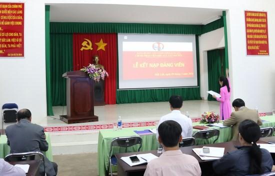 Quần chúng Trần Thị Mai Tuyên thệ trước cờ đảng, cờ tổ quốc, chân dung chủ tịch Hồ Chí Minh và sự chứng kiến của toàn thể đảng viên trong Chi bộ