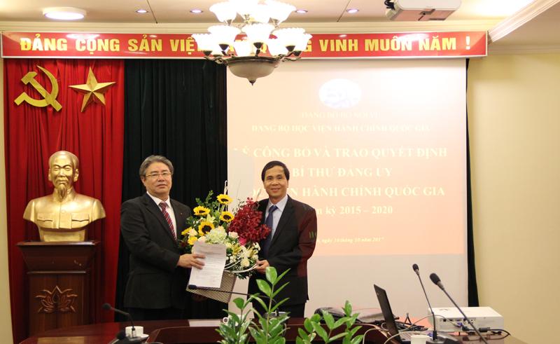 Đồng chí Triệu Văn Cường trao Quyết định và tặng hoa chúc mừng Tân Bí thư Đẳng ủy Học viện Hành chính Quốc gia Đặng Xuân Hoan