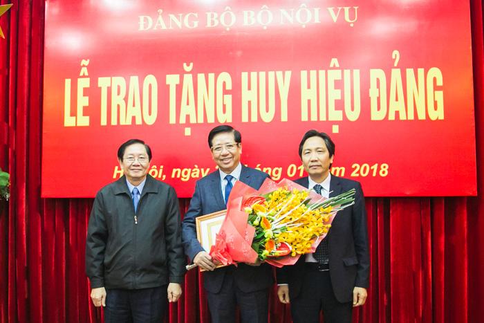 Bộ trưởng Bộ Nội vụ Lê Vĩnh Tân trao Huy hiệu 50 năm tuổi Đảng, Thứ trưởng Bộ Nội vụ Trần Anh Tuấn tặng hoa chúc mừng đồng chí Nguyễn Trọng Điều