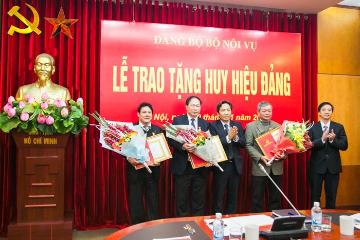 Đồng chí Trần Anh Tuấn và đồng chí Nguyễn Thành Nam trao Huy hiệu 30 năm tuổi Đảng và tặng hoa chúc mừng các đồng chí Vũ Trọng Hách, Phạm Đức Chính và Hà Anh Tuấn