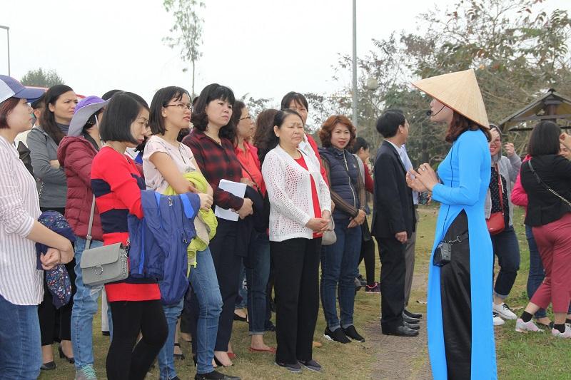 Hướng dẫn viên du lịch giới thiệu với đoàn về Làng Văn hóa các dân tộc Việt Nam