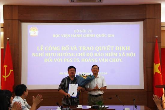 NGƯU. TS. Vũ Thanh Xuân, Phó Giám đốc Học viện tao quyết định và  tặng hoa chúc mừng PGS. TS. Hoàng Văn Chức